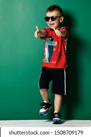 Happy screaming kid boy in blue sunglasses, sneakers, shorts and red t-shirt with crocodile print is laughing showing thumbs up with both hands and stamping on green background