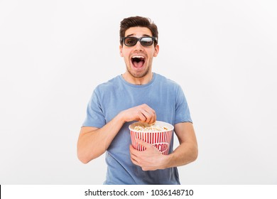 Happy screaming man in t-shirt and 3d glasses holding bucket with popcorn and looking at the camera over grey background