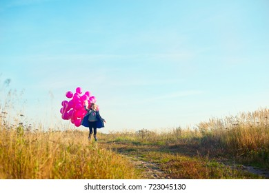 Happy screaming toddler birthday school girl running with colorful balloons in autumn field