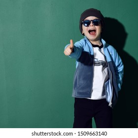 Happy screaming yelling cool kid boy in blue sunglasses, headwear, fleece jacket, white t-shirt and pants showing thumb up on green background with free text copy space