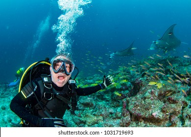 happy scuba diver  yelling oh my god at Manta in the blue background while diving maldives