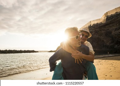 Happy senior adult caucasian couple in love. the man carry on his back the beautiful woman and both smiles. affective and together forever life concept in vacation time ith sunset backlight and ocean