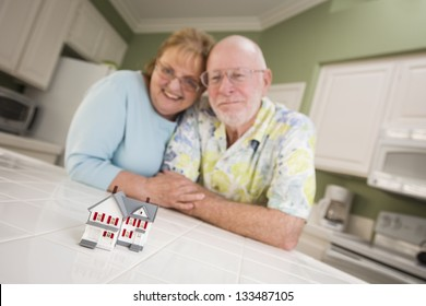 Happy Senior Adult Couple Gazing Over Small Model Home on Their Kitchen Counter.