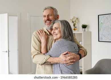 Happy senior adult mature classy couple hugging, bonding, thinking of good future. Carefree cheerful mid age old husband embracing wife looking away dreaming, enjoying wellbeing and love in new house.