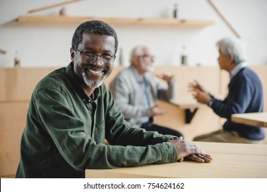 happy senior african american man sitting in cafe and looking at camera