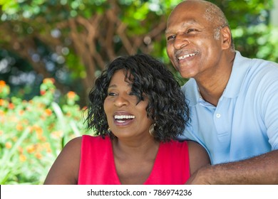 A happy senior African American man and woman couple in their sixties outside together smiling.