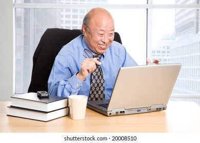 A happy senior asian businessman working in the office