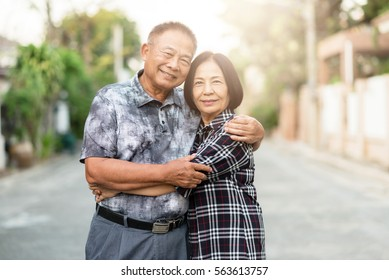 Happy senior Asian couple embracing each other and smile outdoor.
