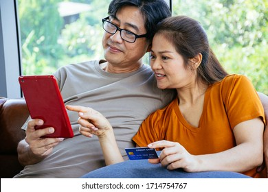 Happy senior Asian couple are looking at their tablet with a credit card ready to pay at the living room in their home