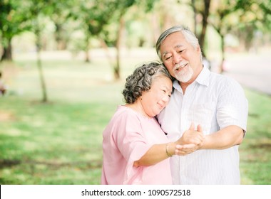 Happy senior Asian couple in love dancing in the park in sunny day