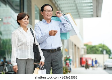 Happy senior Asian couple with many paper-bags after shopping