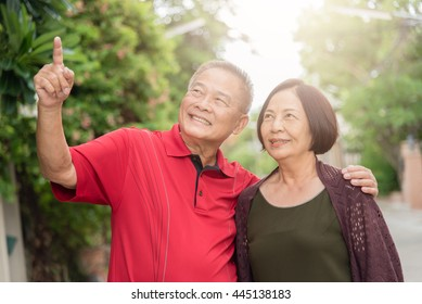 Happy senior Asian couple outdoor with man pointing into distance.Warm tone photo with sunlight.