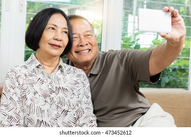 Happy senior Asian couple smiling and taking selfie by mobile smart phone at home