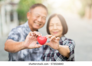 Happy senior Asian couple smiling while holding heart together outdoor. Selective focus on heart.