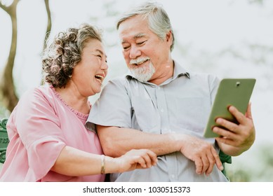 Happy senior Asian couple using digital tablet together outdoor