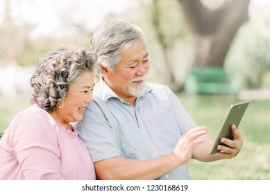 Happy senior Asian couple using digital tablet while sitting in the park