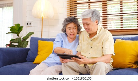 Happy senior asian couple using digital tablet computer sitting on sofa at home living room background, senior people and technology lifestyles