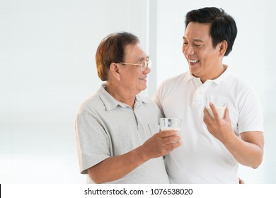 Happy senior Asian man hugging his adult son and drinking milk