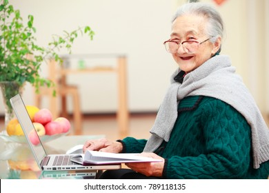 happy senior asian woman using laptop in home