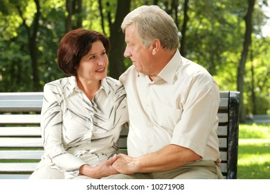 Happy senior attractive couple embracing at park