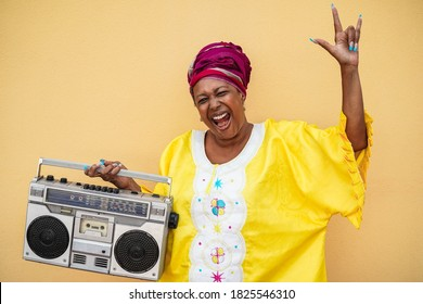 Happy senior black woman with traditional african dress dancing holding vintage stereo - Focus on face