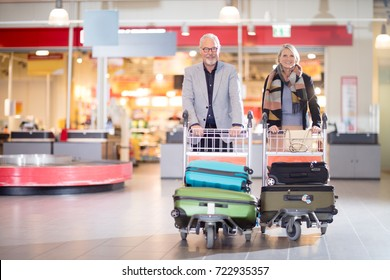 Happy Senior Business Couple With Luggage In Carts At Airport