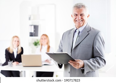 Happy senior businessman with documents standing in the office. Looking at camera. Selective Focus.
