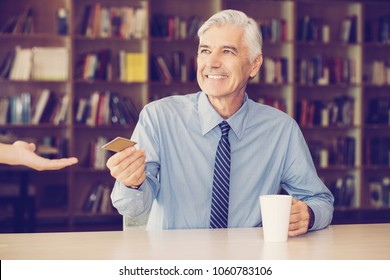 Happy senior businessman giving credit card to waitress to pay for coffee. Positive manager drinking coffee at table in library. Banking or convenient service concept