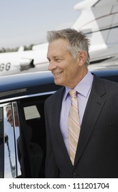 Happy senior businessman standing by car at airfield