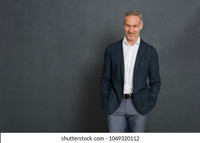 Happy senior businessman standing over grey wall and looking at camera. Portrait of successful leader standing isolated gray background with copy space. Handsome mature man with fashion clothes.