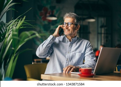 happy senior businessman using cellphone in cafeteria on coffee break