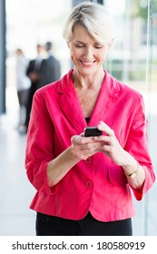 happy senior businesswoman using smart phone in office