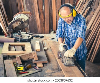 Happy senior carpenter using an electric planer with a wooden plank in the carpentry workshop. Manufacture of wood products.