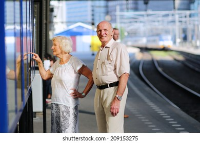 Happy senior caucasian couple travelling around Europe waiting for train in railway station platform in Amsterdam - active retirement concept