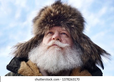 Happy senior caucasian man with splendid mustache and beard against blue sky background. Portrait from below up of elderly stylish hipster wearing a fur cap with tabs over the ears.