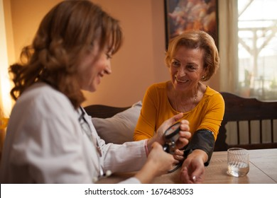 Happy senior Caucasian woman having blood pressure test performed by a mid adult doctor during house call visit and medical examination