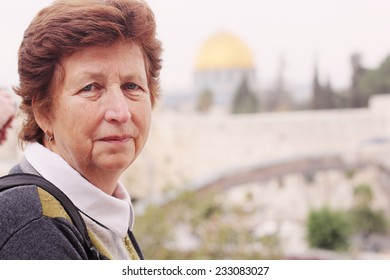 Happy senior caucasian woman travelling in the streets of Jerusalem - active retirement concept