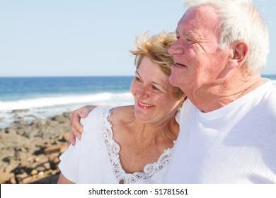 happy senior citizen couple hugging on beach