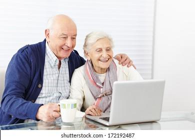 Happy senior citizen couple using laptop computer at home