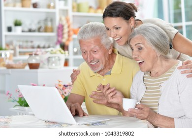 happy senior couple with adult daughter using laptop