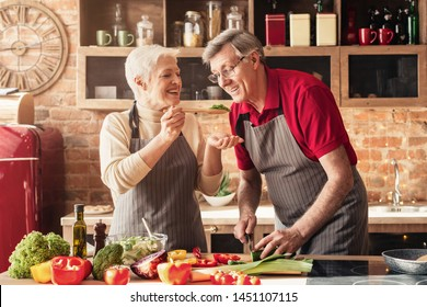 Happy senior couple in aprons tasting food and smiling, cooking healthy lunch together in kitchen