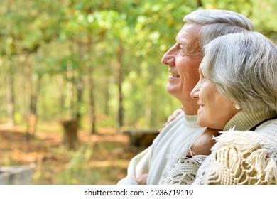 Happy senior couple in autumn park hugging