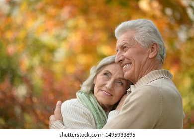 Happy senior couple in autumn park hugging