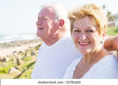 happy senior couple at beach on a sunny day