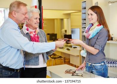 Happy senior couple buying new glasses at optician