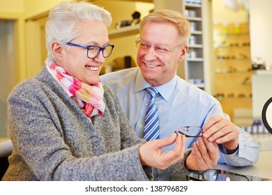 Happy senior couple buying new glasses at the optician