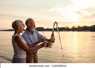 Happy senior couple celebrating with champagne at the riverbank