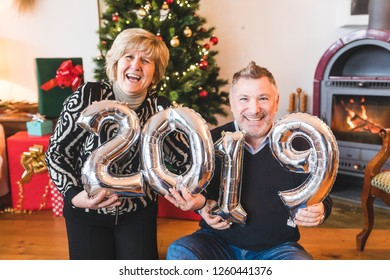 Happy senior couple celebrating new year 2019. Adult man and woman smiling, laughing and holding 2019 balloon sign on new year's eve celebrations. Lifestyle and holidays