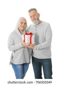 Happy senior couple with Christmas gift on white background