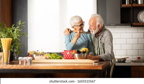 Happy senior couple cooking a meal together at home, smiling woman  feeding  his husband